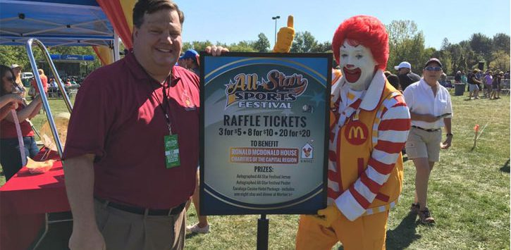 a man standing in front of a raffle ticket sign with Ronald McDonald