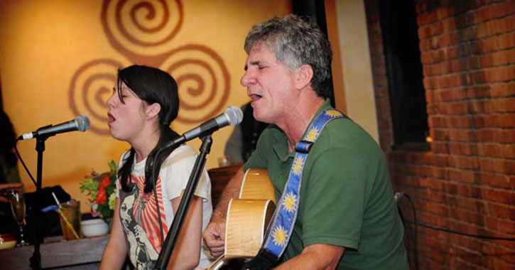 a young woman and older man performing music together on stage