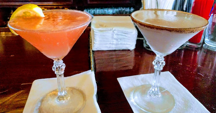 two martinis, one pink lemonade and one chocolate-y, on a bar